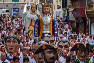 People watch the parade of gigantes y cabezudos (giants and big-headed puppets)