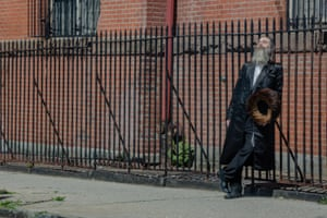A man rests in the sun against a barred fence in Brooklyn, New York on April 14th. Photo by Jordan Gale