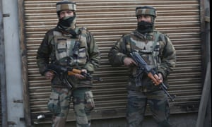 Indian soldiers stand guard after a militant attack on their convoy in Pulwama