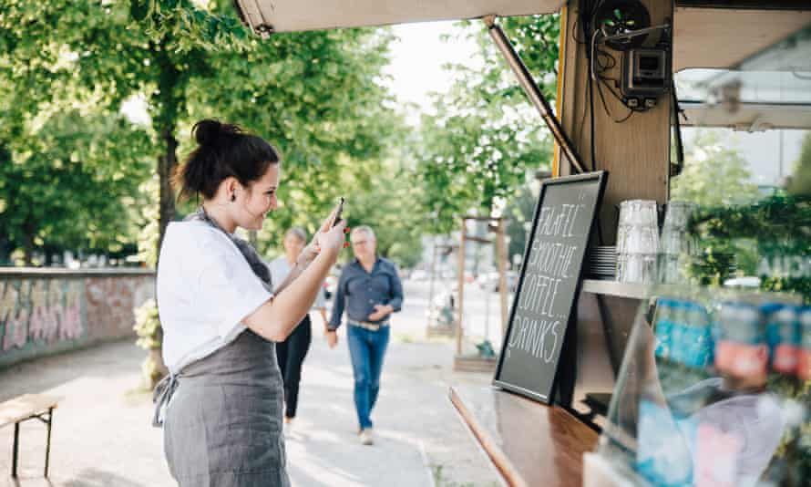 Female owner photographing board through smart phone while standing by food truck