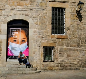 """A man reading a book next to a poster that says """"Covid-19, open your Eyes"""", in Barcelon, Spain."""