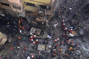 Rescuers stand at the site of the fire in Dhaka on Thursday morning.