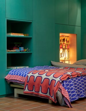 Green light: a teal wall cupboard next to a bed fitted into a snug alcove.