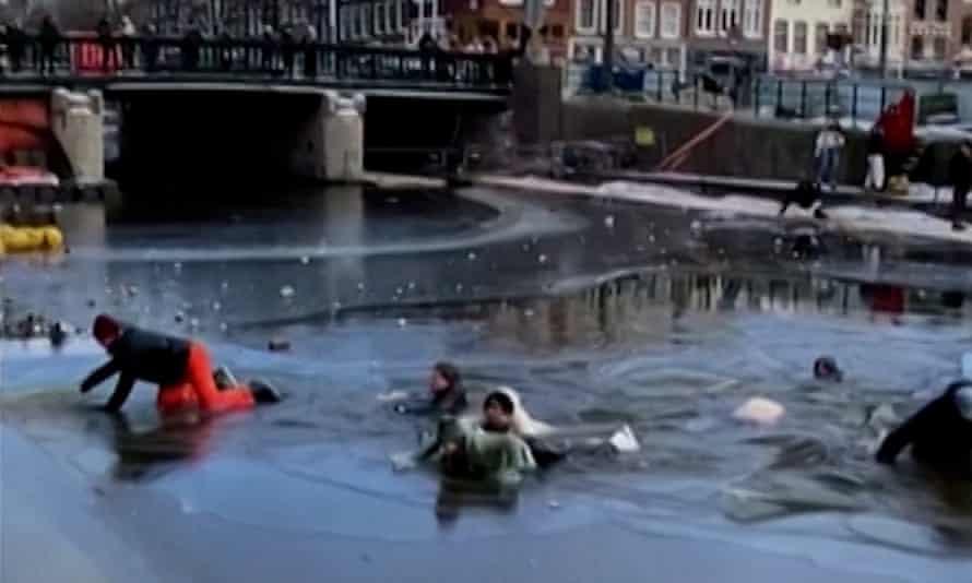 Un grupo de esquiadores cae sobre el hielo en los canales de Ámsterdam el domingo.
