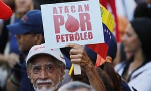 A man holds a sign that reads in Spanish 'They attack for oil' during a march of in support of the state-run oil company PDVSA, in Caracas on Thursday.