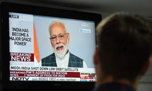 A man watches Indian Prime Minister Narendra Modi's address to the nation on a local news channel