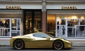 a gold sports car outside a Chanel shop