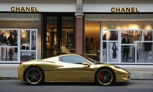 a gold luxury sports car outside a Chanel store