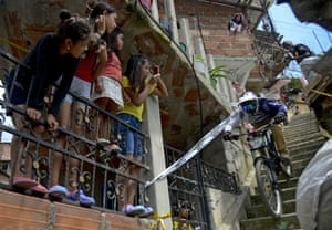 Children watch as a downhill rider competes during the Adrenalina Urban Bike race final