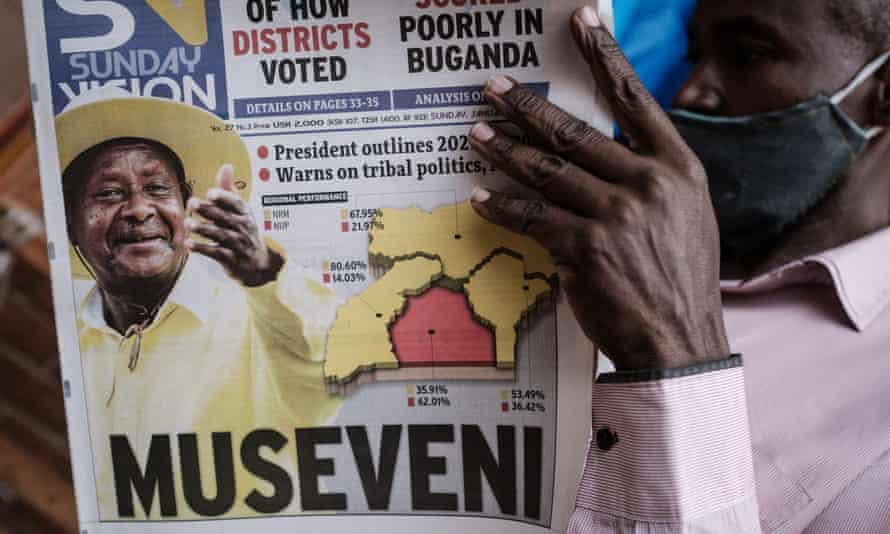 A man reads the Sunday Vision newspaper which shows a portrait of Yoweri Museveni
