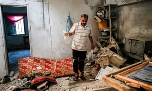 A relative of 23-year-old Palestinian Enas Khammash, who was killed along with her daughter in an Israeli airstrike, inspects their damaged home