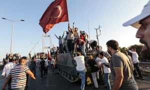 Erdoğan supporters wave flags as they capture a tank