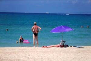 People sunbathe and swim on El Arenal beach, amid the outbreak of coronavirus in Palma de Mallorca, Spain, 15 August, 2020.