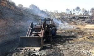 A burnt digger on a farm near the village of La Torre de l'Espanyol, in Tarragona, Catalonia.
