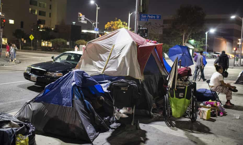 A police car stops beside tents on Skid Row in Los Angles, California.