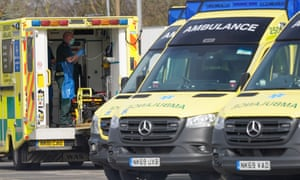 A paramedic prepares the back of an ambulance.