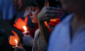 Mourners bow their heads in prayer as they gather for a vigil at the scene of a mass shooting in Dayton, Ohio.