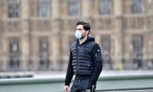 A pedestrian wears a protective face mask in central London