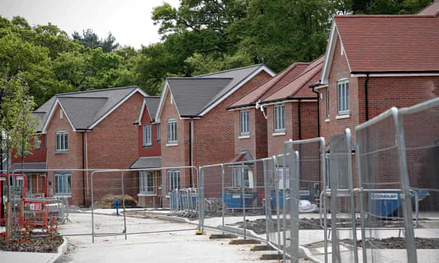 A row of houses behind temporary security fencing