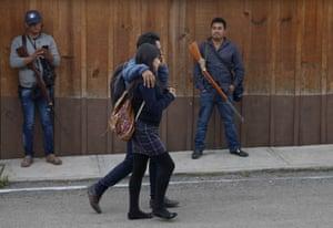Students pass FUPCEG vigilantes outside the group's base in Filo de Caballos.