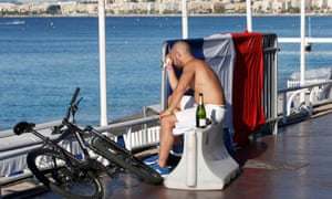 A man sits near a French flag along the beachfront in Nice