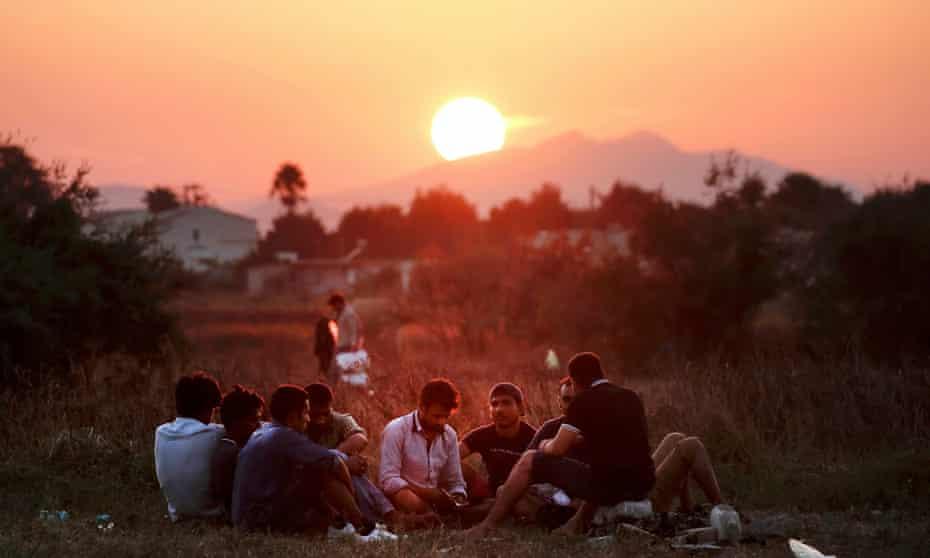 Migrants from Pakistan rest in a field on the Greek island of Kos