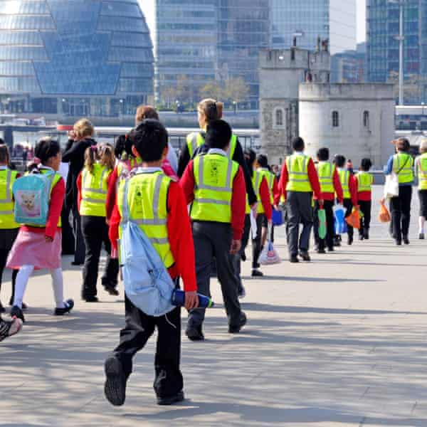 School trip pupils and adults wearing high visibility jackets on visit to The Tower of London