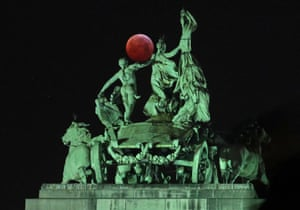 The moon is seen beside a quadriga on the top of the Cinquantenaire arch in Brussels, Belgium