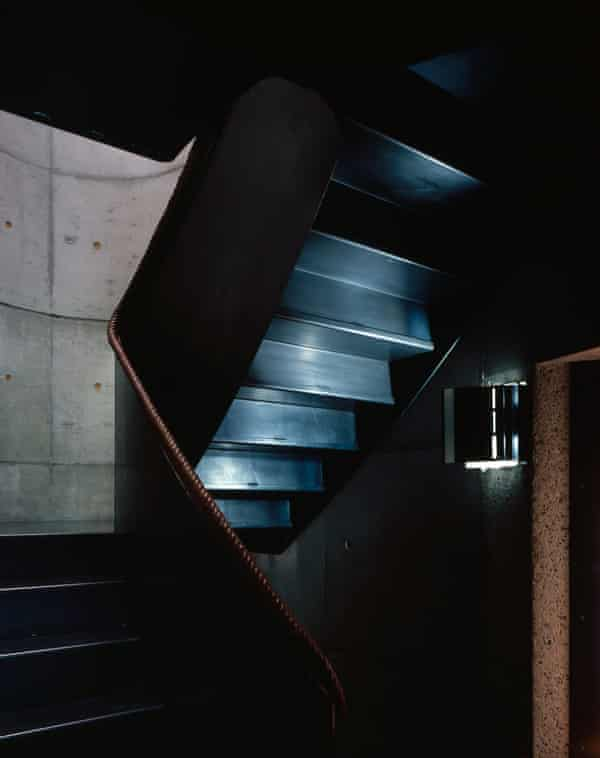 The black steel staircase with leather-covered rope handrail.