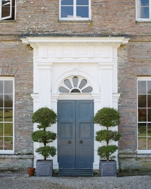Detail of ornate front door with potted trees at each side