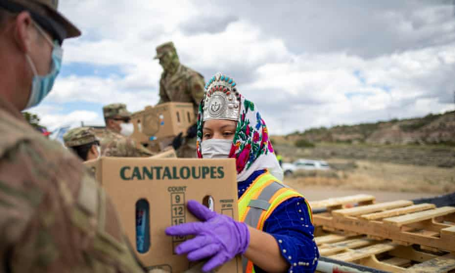 Miss Navajo Nation Shaandiin P Parrish grabs a box of food and other supplies to distribute to families on the Navajo Nation Reservation, New Mexico.