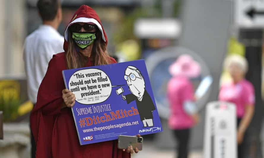 A protester dressed as a handmaiden stands outside the venue in Louisville.
