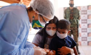 A member of the Brazilian Armed Forces medical team examines a child at a community school in the indigenous village of Morro Branco.