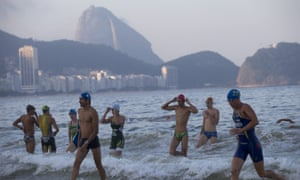 Triathletes leave the water after swimming in the Copacabana beach