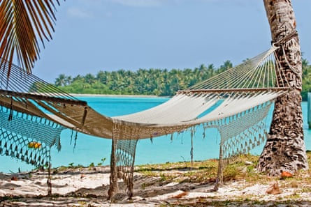A tattered hammock hangs between palm trees on Direction Island in Cocos Keeling