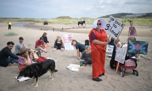 Protesters, including a 'handmaid', gather on the beach near Turnberry