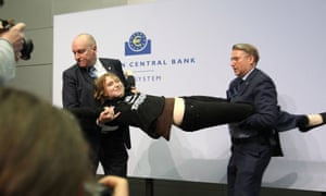 A woman is stopped by security after she interrupted a press conference by Mario Draghi