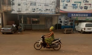 A Fespaco festival-goer arrives on her motorbike early on Sunday morning for the first screening of the day at Ciné Burkina.