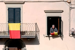 A resident holds a flag bearing the colours of the Tuscan village
