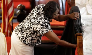 A church member places a black cloth on the chair of the Reverend Clementa Pinckney