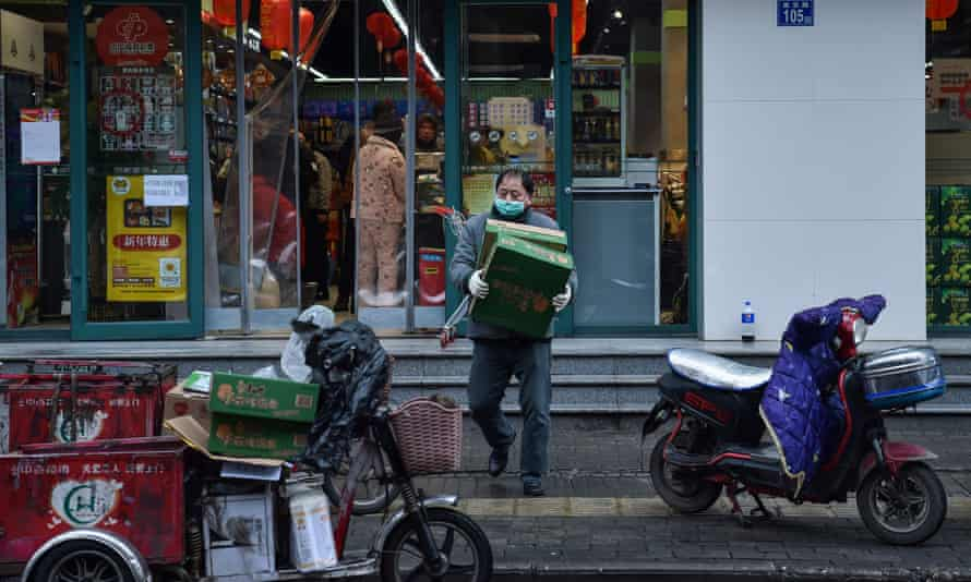 A man wearing a protective face mask carries boxes at a market in Wuhan