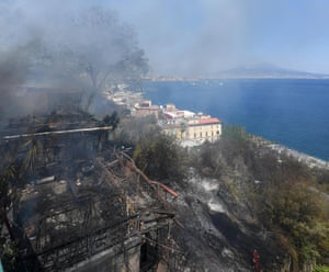 Smoke arises from burning vegetation after a fire on Posillipo hill, in the heart of Naples, Italy