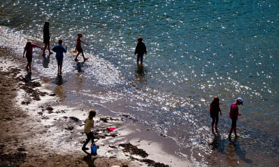 Children play on the beach in Port Isaac, Cornwall.