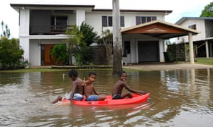 Children float past houses surrounded by flood waters in the town of Ingham, in north Queensland.