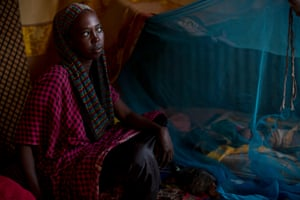 Muna Abukar, 15, sits next to her four-month-old twins under a mosquito net at her relatives' home near Burao
