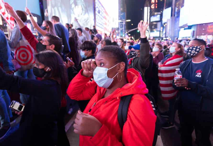 A woman wipes a tear as she watches Kamala Harris's speech on a big screen in Times Square, New York.