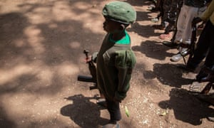A newly released child soldier stands with his rifle during a release ceremony in Yambio