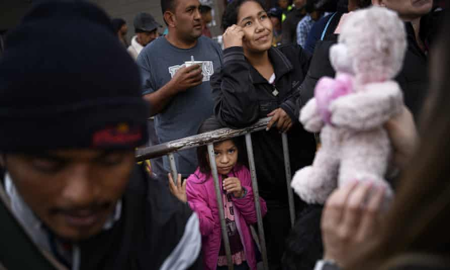 A girl from Honduras waits for a present given by a nongovernmental organization outside an empty warehouse used as a shelter for migrants.