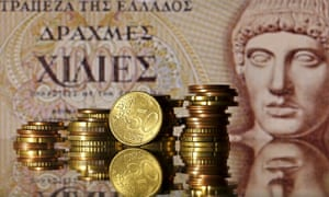 Euro coins in front of an old Greece drachma banknote.