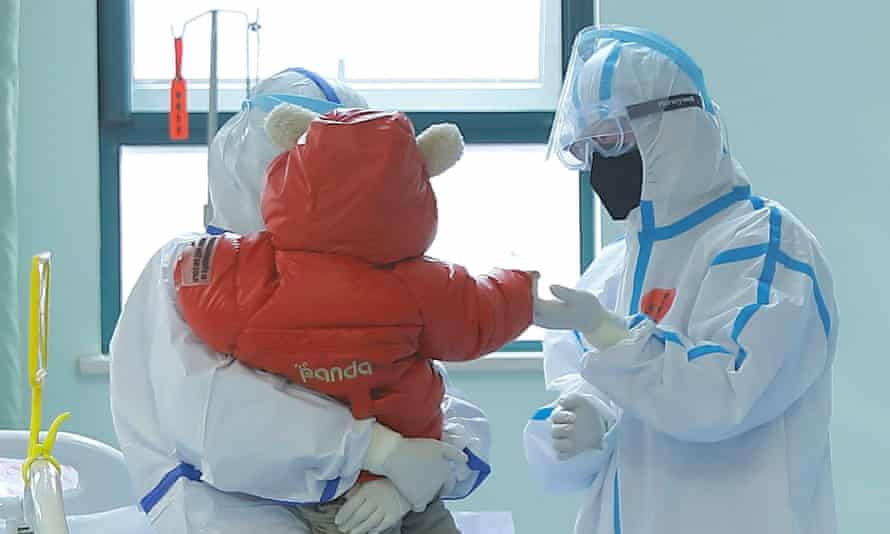 a small child with two people in PPE in a hospital room